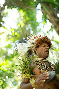 Man in traditional dress performs with traditional instruments, Mclaren Harbour, Tufi, Cape Nelson, Oro Province, Papua New Guinea