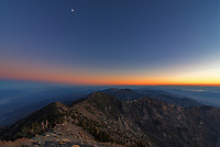 """Complete silence surrounded the 11,049' summit of Telescope Peak as the colors of sunset faded away and twilight deepened. This peak at the top of Death Valley National Park is so named because """"You could see no further with a telescope."""" Endless ridges, mountains, sand dunes, and salt flats stretched out in every direction. In the valley on the left is Badwater Basin. Nowhere in North America is lower or dryer, and it lays claim to the hottest air temperature ever measured (134°F). Despite being only 18 miles away, the weather and environment up here at this altitude is vastly different. Temperatures can be as much as 60°F cooler, and a lot more rain and snow falls here than in the surrounding desert. This sustains a forest of bristlecone pines, the oldest species of tree on Earth at up to 5,000 years old. Staying on the summit for the sunset meant descending 8 miles in the dark, but the incredible views were worth the longest dayhike I've ever done."""