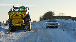© Licensed to London News Pictures. 26/01/2013..North Yorkshire Moors, England..A car drives past as tractors clear snow from a road following heavy overnight snowfall on the North Yorkshire moors...Photo credit : Ian Forsyth/LNP