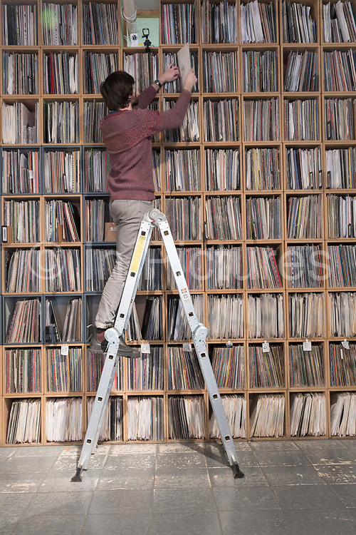 A man on step ladders searching for vinyl on shelves stacked high with records at Vinyl Pimp record shop in Hackney Wick on the 29th March 2018 in East London in the United Kingdom.