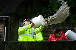 Memories return of June 2007 as heavy rains cause more flooding in Sheffield. Two houses on Ecclesfield Common are threatened by flood waters from over-flowing streams as police officers battle against the waters with buckets and hand shovels  09 June 2009 Copyright Paul David Drabble