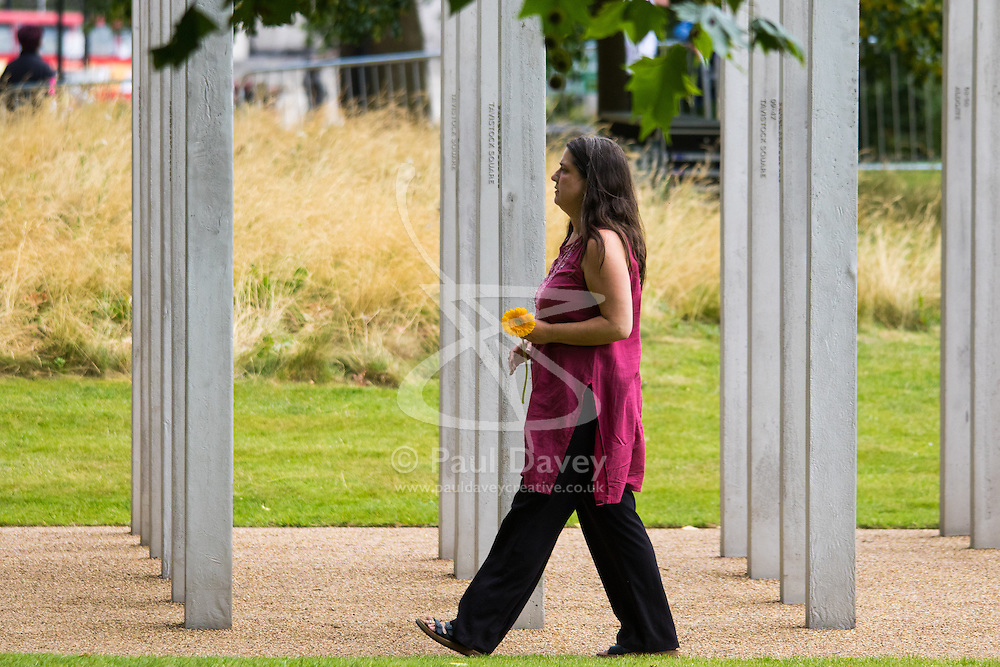 Hyde Park, London, July 7th 2015. Families of the victims and survivors of the 7/7 bombings in London gather at Hyde Park and are joined by the Duke of Cambridge Prince William at an emotional service commemorqating the Islamist terrorist bombing outrage that happened on London's transport network, claiming 57 lives and left scores of people injured. PICTURED: Esther Hyman, sister of Miriam who perished on 7/7 lays a single yellow gerberer at the memorial.