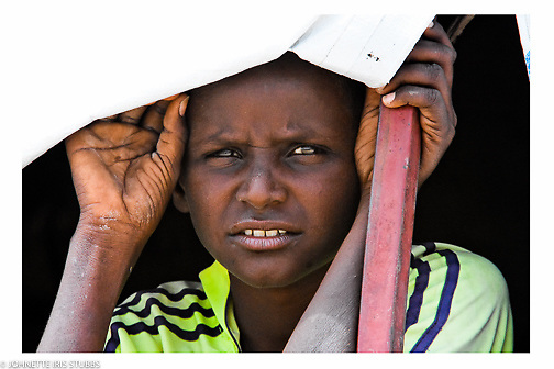 Young boy looks from the windo of his temporary shelter in Asaita Refugee Camp, Afar, Ethiopia 2016