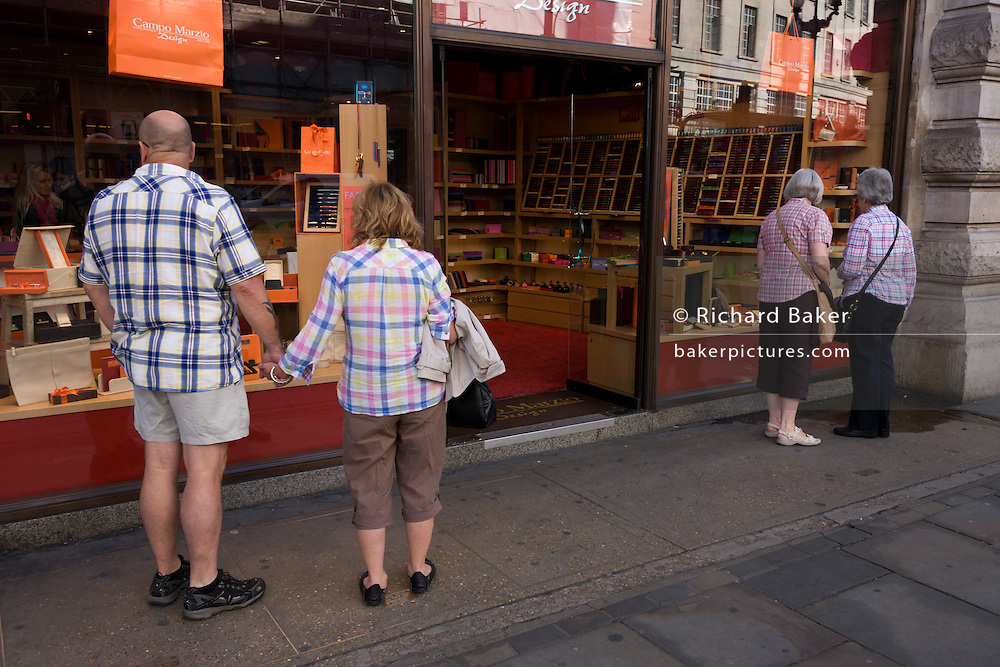 Visitors to London all wearing different checkered patterns look in a design shop in Regent Street, Westminster.