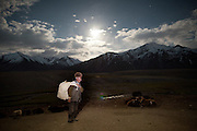 Under a full moon. Rahman Qul has just picked up dry dung to use as fuel for heating and cooking in his yurt, Pamir is way above the tree-line..Summer camp of Muqur, Er Ali Boi's place...Trekking through the high altitude plateau of the Little Pamir mountains (average 4200 meters) , where the Afghan Kyrgyz community live all year, on the borders of China, Tajikistan and Pakistan.