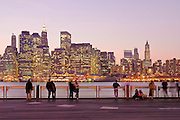 People enjoying the view of Lower Downtown Manhattan skyline seen from the Brooklyn side of the East River showing the skyscrapers of the Financial District at twilight, New York City.