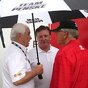 NASCAR Sprint Cup car owners Roger Penske, Richard Childress and Joe Gibbs talk in the rain prior to the 56th Annual NASCAR Coke Zero400 race at Daytona International Speedway on Saturday, July 5, 2014 in Daytona Beach, Florida.  (AP Photo/Alex Menendez)