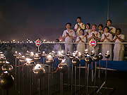 """22 FEBRUARY 2016 - KHLONG LUANG, PATHUM THANI, THAILAND:  A family prays after lighting lamps during the Makha Bucha Day service at Wat Phra Dhammakaya.  Makha Bucha Day is a public holiday in Cambodia, Laos, Myanmar and Thailand. Many people go to the temple to perform merit-making activities on Makha Bucha Day, which marks four important events in Buddhism: 1,250 disciples came to see the Buddha without being summoned, all of them were Arhantas, Enlightened Ones, and all were ordained by the Buddha himself. The Buddha gave those Arhantas the principles of Buddhism, called """"The ovadhapatimokha"""". Those principles are:  1) To cease from all evil, 2) To do what is good, 3) To cleanse one's mind. The Buddha delivered an important sermon on that day which laid down the principles of the Buddhist teachings. In Thailand, this teaching has been dubbed the """"Heart of Buddhism."""" Wat Phra Dhammakaya is the center of the Dhammakaya Movement, a Buddhist sect founded in the 1970s and led by Phra Dhammachayo.     PHOTO BY JACK KURTZ"""