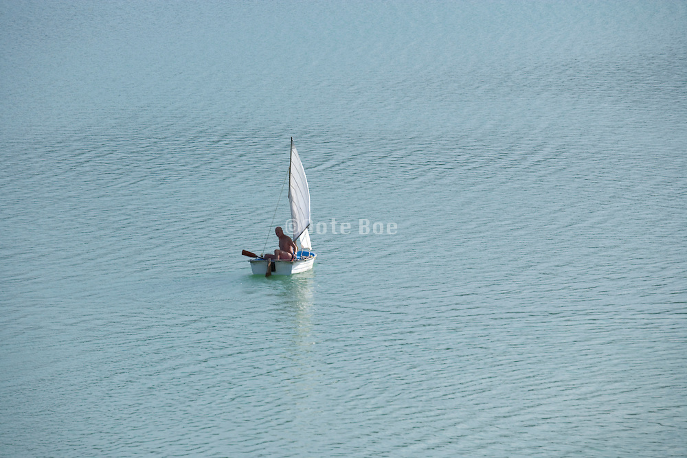 adult male person in a little sailing boat