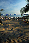 Eary morning on Sanur Beach, with hotel chairs and umbrellas, and footprings in the freshly raked sand. The  sacred mountain, Gunung Agung, on the horizon. Sanur, Bali, Indonesia.