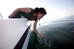 05 May 2010. Venice, Louisiana. Deepwater Horizon, British Petroleum environmental oil spill disaster.<br /> ARCA NASCAR rising star and environmental activist Leilani Munter takes in the unnatural disaster created by BP on a trip into the Gulf of Mexico. Leilani inspects sludge in the water 10 miles south of Venice Marina and approximately 34 miles from the site of the Deepwater Horizon's sunken oil platform. The sludge is a gelatinous mix with the consistency of diarrhea, sometimes clumped together in large masses so thick you can not see the ocean through it. The water, for miles and miles is filled with small pea shaped clumps, most the size of every kind of fish food available from small fish shape to shrimp to plankton. It is everywhere. The sheen on the surface is everywhere. It stretches for miles and miles and miles and miles and miles. Dead Jellyfish shrivel in the mix, the main seafood of turtles passing through at this time of year. What have we done?<br /> Photo credit; Charlie Varley/varleypix.com