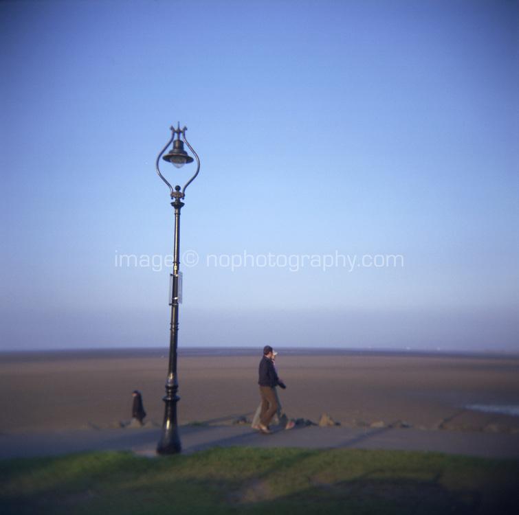 People walking along Sandymount strand in Dublin Ireland late afternoon in the winter