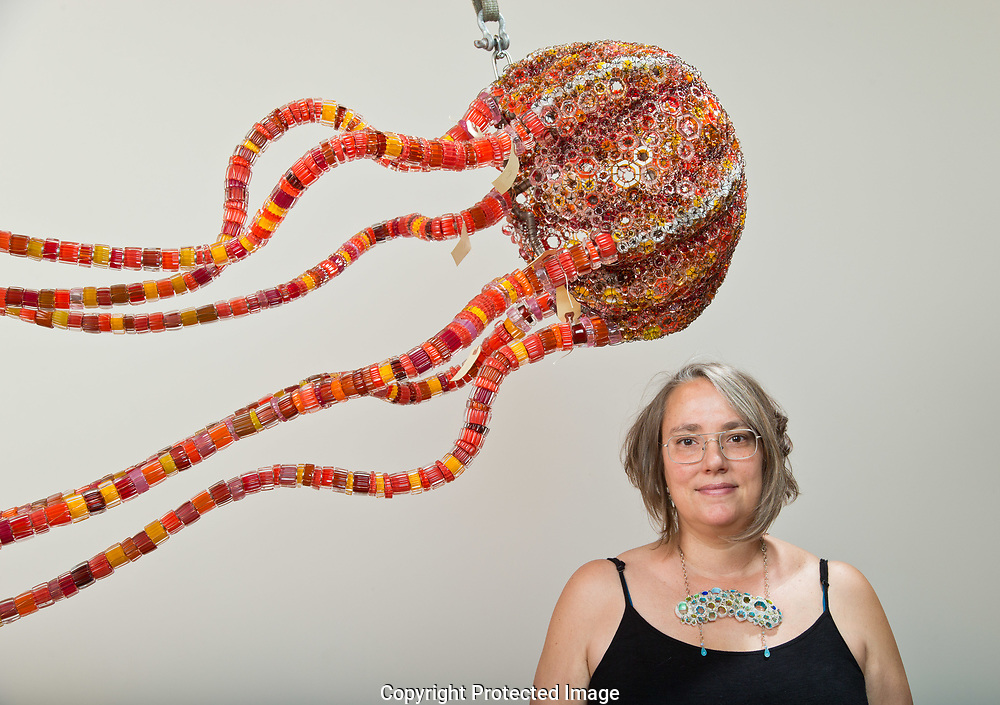 Kait Rhoads working on a glass sculpture in her Seattle studio that will hang in the new aquarium<br /> at Point Defiance Zoo and Aquarium, Thursday, July 5, 2018. (Photo/John Froschauer)