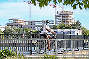 A local resident wearing facemask cycles across the dockland path nearby Excel Exhibition Centre where the London NHS Nightingale Covid19 makeshift Hospital is located on Wednesday, May 20, 2020. The government decided not to accept further patients to the facility. (Photo/ Vudi Xhymshiti)