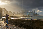 Fisherman fishing from Malecon road during storm, Havana, Cuba