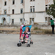 14 month old Yazidi girl Asma Aisam Ismail outside the abandoned Lepida psychiatric hospital in whose grounds the Leros 'Hot spot' (an EU-run migrant's reception centre) has been built. Her mother, Torko Haji Khalaf, 21, picks figs in the background. <br /> <br /> Originally constructed, in 1930 by fascist Italy, as barracks for Italian soldiers serving in the aeronautical base of Portolago, it was then, for a short period after WWII, a re-education camp for the children of Greek Communists. In 1958, it was converted into the biggest psychiatric hospital in the country. The conditions for the patients were horrific and it was shut down in the late 1980s and the patients moved into smaller buildings in the grounds and elsewhere on the island.