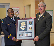 Assistant Chief Michael Benford, left, honors retired officer Joseph Jackson, right, during the Houston ISD Police awards banquet at Thompson Elementary School, August 15, 2014.