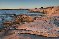 Granite shoreline of Peggy's Cove glowing pink in the light of the setting sunNova Scotia