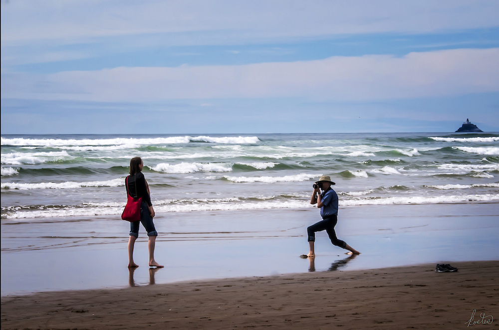 Portrait of a man taking a photo of his girlfriend at the beach.