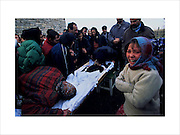 A girl cries at the funeral of her seventeen year old sister who died from tuberculosis, an illness which still hits poverty stricken communities. Timisoara, Romania December 2003..Roma Gypsies left Rajasthan in India a thousand years ago, in the ninth and tenth centuries. They were pushed west by the Ottoman Muslim Empire as it moved through Persia towards the frontiers of Europe. They entered Europe in the foutrteenth century and were slaves in Romania and Moldavia until the mid 1850s. There are about 15 million Roma gypries in the world, about 12 million who live in Europe. they are Europe's largest ethnic minority. They have rich traditions and culture, their own language. They are renowned for their prowess in music and dance; they are also skilled craftsman, metal roofmakers, silver and goldsmiths. Their traveling and nomadic lifestyle which grew from a necessity to find work, and because they were often moved on from one place to the next, has given them both a liberty but also marks them as different and they are often feared by sedentary peoples, who label and scapegoat them. They are hardy survivors and live in the brunt of racism and prejudice, often marginalised, living in poverty, without proper human rights afforded to them..