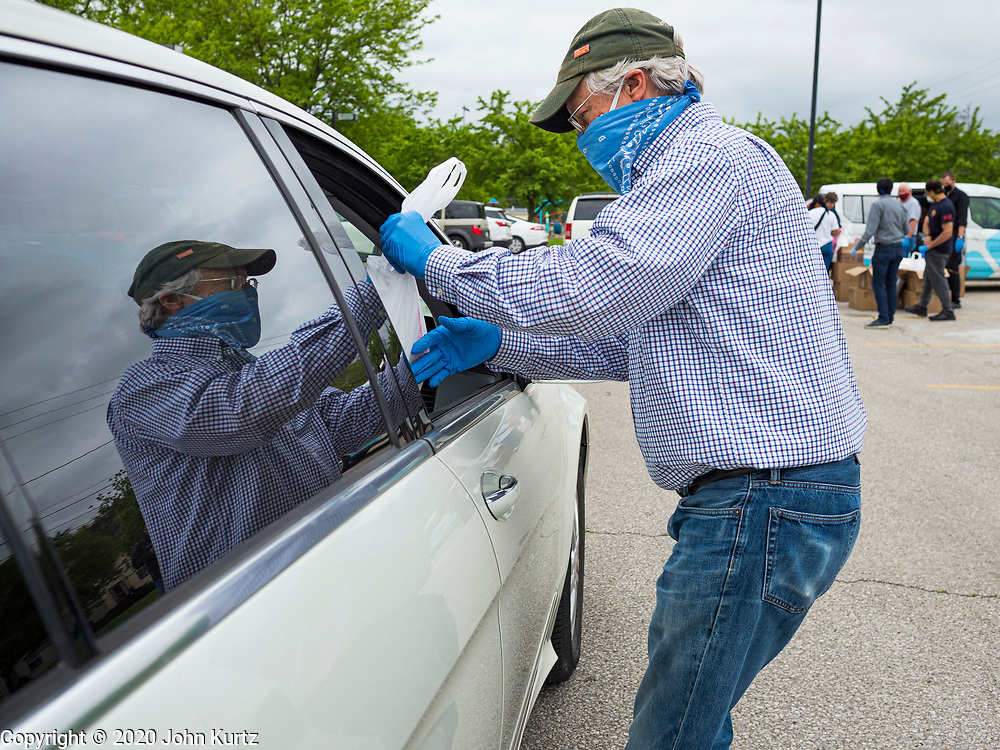 21 MAY 2020 - DES MOINES, IOWA: FRANK COWNIE, the mayor of Des Moines, hands a bag of meals to people in a drive through emergency food distribution in Evelyn K. Davis Park in central Des Moines. All of the 485 meals were distributed in about an hour. The economic fallout of the pandemic is being felt throughout Iowa. On May 21, 2020, Iowa reported that 187,375 people had filed for unemployment since the beginning of the COVID-19 pandemic and resulting economic shutdown. Emergency food pantry has also increased in that time, as many Iowans in low wage jobs used emergency food banks and pantries for the first time. The Food Bank of Iowa said Thursday that demand in April 2020 was 31% higher than demand in April 2019, mostly because of unemployment caused by the Coronavirus (SARS-CoV-2) pandemic. The emergency food distribution Thursday was organized by the city of Des Moines, Food Bank of Iowa, Central Iowa Shelter and Services, Urban Dreams and Orchestrate Hospitality.      PHOTO BY JACK KURTZ
