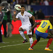 DeAndre Yedlin, (left), USA, passes the ball past Walter Ayoví, Ecuador, during the USA Vs Ecuador International match at Rentschler Field, Hartford, Connecticut. USA. 10th October 2014. Photo Tim Clayton