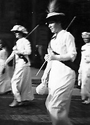 Photograph of Matilda Gardner and three other unidentified women in background marching in suffrage procession, holding a baton, wearing feathered hat, long white dress, and sash with lettering across chest. ca. 1913.