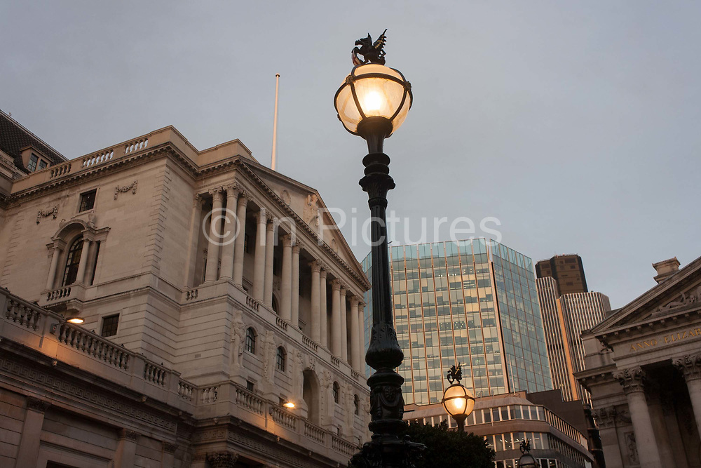 Early evening lighting illuminates the street, below the Bank of England, on 9th December 2016, in the City of London, England. The Bank moved to its current location in Threadneedle Street in 1734, and thereafter slowly acquired neighbouring land to create the edifice seen today. Sir Herbert Bakers rebuilding of the Bank, demolishing most of Sir John Soanes earlier building, was described by architectural historian Nikolaus Pevsner as the greatest architectural crime, in the City of London, of the twentieth century.
