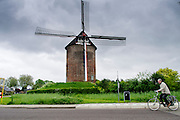 Een oudere man fietst voorbij de Buitenmolen in Zevenaar, een plaats in de streek De Liemers in het oosten van Nederland.<br /> <br /> An older man cycle past the Buitenmolen in Zevenaar, a place in the region's Liemers in the east of the Netherlands.