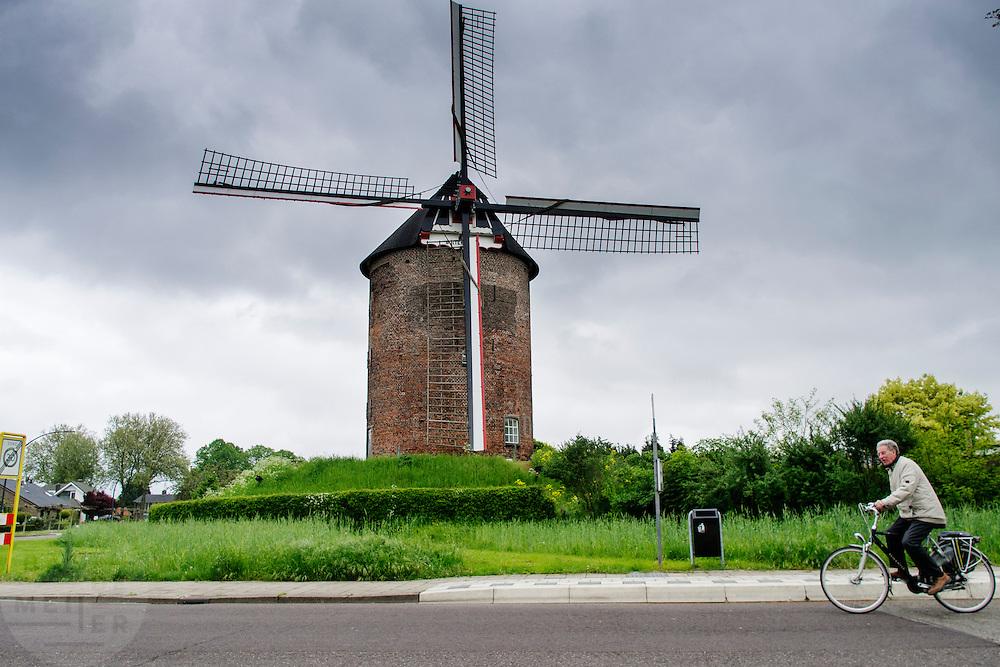 Een oudere man fietst voorbij de Buitenmolen in Zevenaar, een plaats in de streek De Liemers in het oosten van Nederland.<br /> <br /> An older man cycle past the Buitenmolen in Zevenaar, a place in the region's Liemers in the east of the Netherlands.
