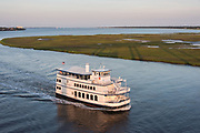 Sunset tour boat Spirit of Carolina crosses the Ashley River past the saltwater marsh at sunset in Charleston, South Carolina.