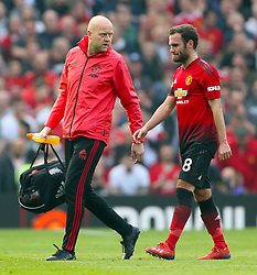 Manchester United's Juan Mata leaves the pitch with medical staff