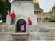 "18 MAY 2020 - DES MOINES, IOWA: Children of ""anti-vaxxers"" climb on a memorial to the pioneers who settled in Iowa. About eight adults, and their children, gathered in the front of the Iowa State Capitol in Des Moines Monday for a prayer vigil against mandatory vaccines. Iowa state law allows the governor to mandate vaccines for communicable diseases during a public health emergency and the ""anti-vaxxers"" are afraid the government will mandate a vaccine for Coronavirus (SAR-CoV-2) if one is developed. As of May 18, 355 people in Iowa have died from COVID-19, the disease caused by the Coronavirus (SARS-CoV-2), and 14,955 have tested positive for the Coronavirus.               PHOTO BY JACK KURTZ"