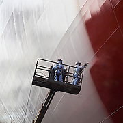 side of ship being spray painted red