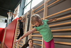 Three girls exercising on wall bars in large gym, Munich, Bavaria, Germany