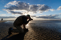 Photographer on beach photographing patterns in sand, Gulf of Mexico, East Beach, Galveston, Texas, USA