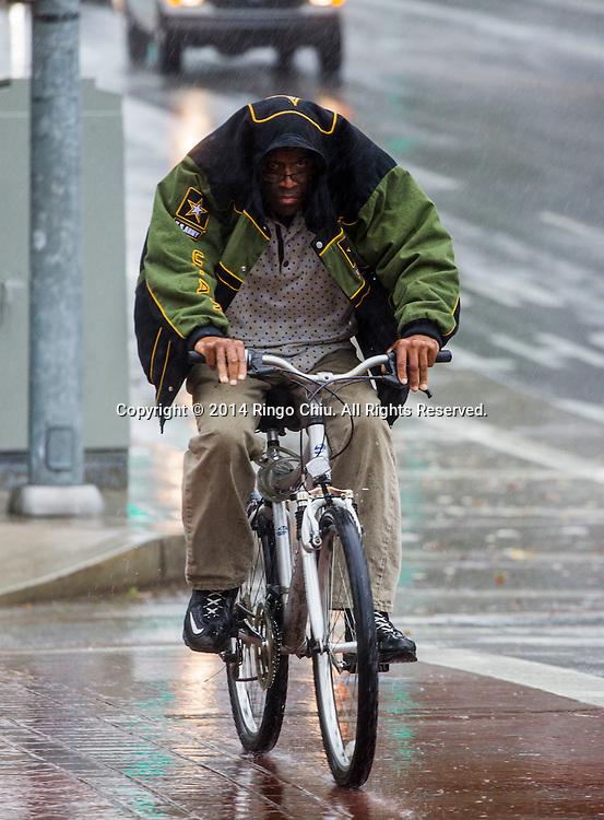 12月2日,美國加利福尼亞州洛杉磯,一名男子冒雨在市中心路上騎自行車。當天南加州迎來秋天第一場暴雨,將為今年面臨嚴重乾旱問題的加州帶來2至5寸雨水。 同時,當局亦發出警告,洪水、土石流可能會襲擊部分地區。 (新華社發 趙漢榮攝)<br /> A cyclist covering himself with a jacket rides down the street in downtown Los Angeles, California, Tuesday, December 2, 2014. California is bracing for the arrival of a new, more powerful Pacific storm following a weekend of scattered rain, showers and snow. The National Weather Service says a low-pressure system off the coast will draw a plume of subtropical moisture northward into the state beginning on Tuesday.  (Xinhua/Zhao Hanrong)(Photo by Ringo Chiu/PHOTOFORMULA.com)