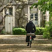 A monk from the monastic community of Solesmes goes to the orchard by bike. 06-05-16<br /> Un moine de la communauté monastique de Solesmes se rend au verger à vélo. 06-05-16