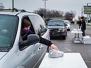 """11 APRIL 2020 - DES MOINES, IOWA: A motorist picks a ready to cook pasta meal from a plastic table during a food distribution in Des Moines. Most non-essential businesses in Iowa are closed until 30 April. Because of business closings causes by the Novel Coronavirus (SARS-CoV-2) pandemic, well over 100,000 Iowans filed first time claims for unemployment in the last three weeks, more than applied during the peak of the Great Recession of 2008. Local food banks have seen an unprecedented spike in people seeking nutritional assistance. Midwest Foods, a Des Moines based company and owner of Ginos Fine Italian Foods, gave away 1,000 complete dinners with sauce, noodles, salad, and dressing Saturday morning. People started lining up 3 hours before the food distribution began. The food distribution was done following """"social distancing"""" guidelines and all of the workers wore masks and gloves.       PHOTO BY JACK KURTZ"""