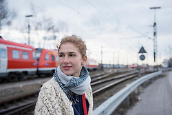 Portrait of a young woman with railway track and red train in the background, Munich, Bavaria, Germany