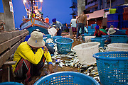 Oct. 6, 2009 -- SAMUT SAKHON, THAILAND: A Burmese worker wipes his brow while he sorts fish just unloaded at the port in Samut Sakhon, Thailand. The Thai fishing industry is heavily reliant on Burmese and Cambodian migrants. Burmese migrants crew many of the fishing boats that sail out of Samut Sakhon and staff many of the fish processing plants in Samut Sakhon, about 45 miles south of Bangkok. Migrants pay as much $700 (US) each to be smuggled from the Burmese border to Samut Sakhon for jobs that pay less than $5.00 (US) per day.   Photo by Jack Kurtz / ZUMA Press