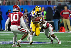 LSU Tigers running back Chris Curry (24) is hit by Oklahoma Sooners safety Justin Broiles (25)) during the first half  in the 2019 College Football Playoff Semifinal at the Chick-fil-A Peach Bowl on Saturday, Dec. 28, in Atlanta. (Vasha Hunt via Abell Images for the Chick-fil-A Peach Bowl)