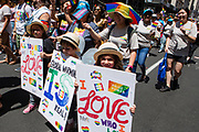 New York, NY - 30 June 2019. The New York City Heritage of Pride March filled Fifth Avenue for hours with participants from the LGBTQ community and it's supporters. Three children carry signes promoting love and attention to global warming.
