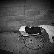 A homeless woman sleeping on a makeshift bed by a grate which serves as the exhaust vent for heating the skyscrapers on at the corner of York Street and Wellington Avenue West located in Toronto's Financial District..(Credit Image: © Louie Palu/ZUMA Press).