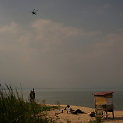 An army helicopter flies by as locals enjoy the beach at Lake Tanganyika in Bujumbura.