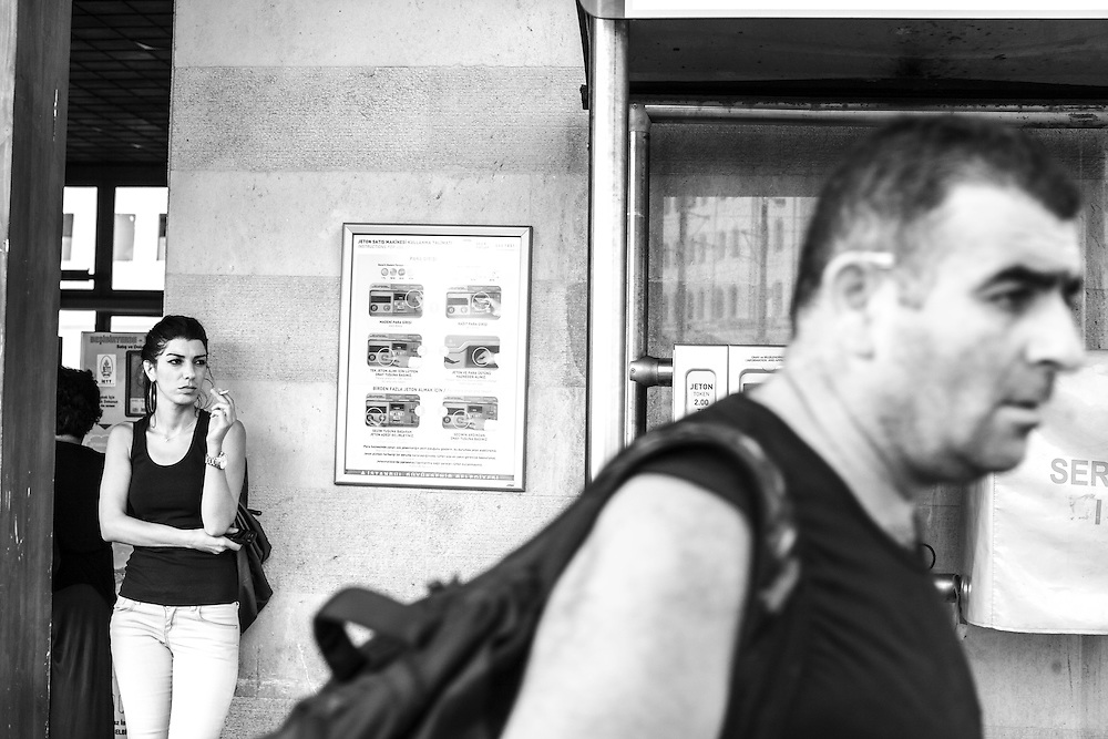 A woman smokes while waiting for a ferry in Eminonü, in Istanbul