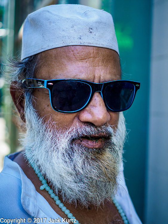 """24 NOVEMBER 2017 - YANGON, MYANMAR: A Muslim man waits to enter Surtee Sunni Jumma Mosque for Friday midday prayers. Many Muslims in overwhelmingly Buddhist Myanmar feel their religion is threatened by a series of laws that target non-Buddhists. Under the so called """"Race and Religion Protection Laws,"""" people aren't allowed to convert from Buddhism to another religion without permission from authorities, Buddhist women aren't allowed to marry non-Buddhist men without permission from the community and polygamy is outlawed. Pope Francis is to arrive in Myanmar next week and is expected to address the persecution of the Rohingya, a Muslim ethnic minority in western Myanmar. Some Muslims and Christians are concerned that if the Pope's comments take too strong of pro-Rohingya stance, he could exacerbate religious tensions in the country.  PHOTO BY JACK KURTZ"""