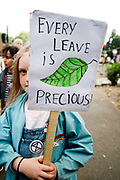 The Air that we Grieve march on July 12th 2019 in East London, United Kingdom. Organised by Extinction Rebellion to draw attention to air pollution and the climate emergency. A young girl holds a placard with a drawing of a leaf saying Every Leave sic is Precious.