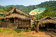 14 MARCH 2013 - BAN PANG SAI, LAOS: A satellite dish for satellite TV sits on a post in front of a tradition home in the village of Ban Pang Sai in Luang Namth province of northern Laos. PHOTO BY JACK KURTZ
