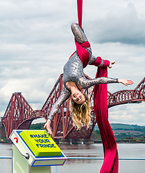 EMBARGOED TILL 10:00 5 JUNE 2019<br /> <br /> Pictured: Fringe Programme Launch. Forth Rail Bridge, South Queensferry, Scotland, United Kingdom, 04 June 2019.<br /> <br /> An aerial artist, Blaise Donald, wearing a sparkling costume performs in front of the iconic bridge launching the Edinburgh Festival Fringe programme and this year's Fringe hashtag #MakeYourFringe.<br /> <br /> Sally Anderson | EdinburghElitemedia.co.uk
